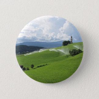 Ridge on alpine pasture with grass sprinklers button
