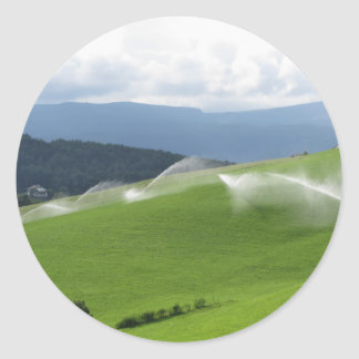 Ridge on alpine pasture with grass sprinklers classic round sticker