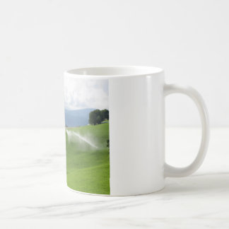 Ridge on alpine pasture with grass sprinklers coffee mug