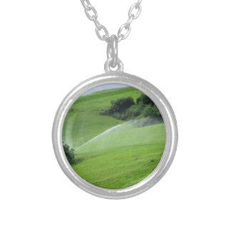 Ridge on alpine pasture with grass sprinklers round pendant necklace