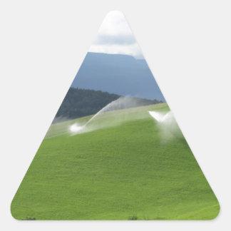 Ridge on alpine pasture with grass sprinklers triangle sticker