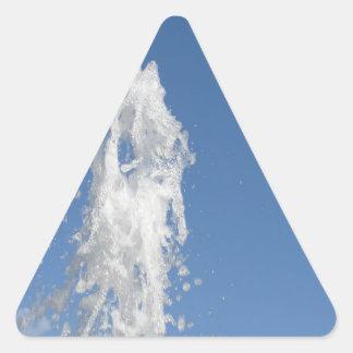 Riegue la rociadura de una fuente contra el cielo pegatina triangular