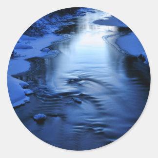 Río helado y nevoso con el azul del invierno