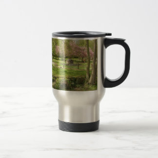 River front pink flowers of prunus in a park travel mug