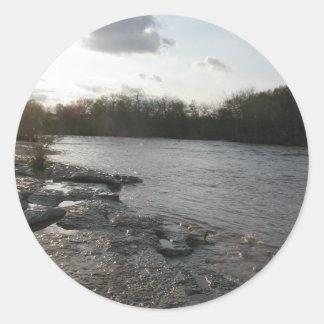 Riverbank en la puesta del sol pegatina redonda