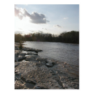 Riverbank en la puesta del sol tarjeta postal