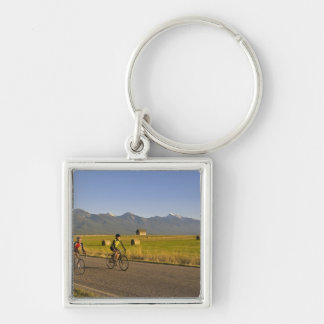 Road bicyclists ride down a back country road key chains