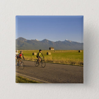 Road bicyclists ride down a back country road pinback button
