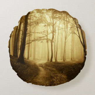 Road in a dark forest with fog round pillow