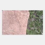 Roca de piedra roja aislada en paisaje verde pegatina