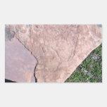 Roca roja agrietada en paisaje verde rectangular pegatina