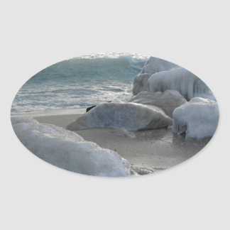 Rocas cubiertas en hielo en la orilla de mar pegatina ovalada