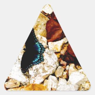Rocas, hojas y mariposa pegatina triangular