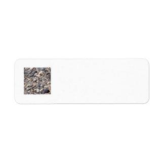 Rocas lavadas óvalo del río en arena gris etiqueta de remite