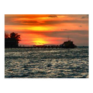 Rod y embarcadero del carrete en la puesta del sol postal