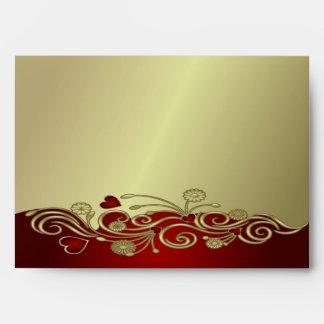 Rojo y corazones y volutas del oro sobres