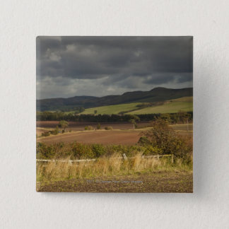 Rolling Hills And Mountains Under A Cloudy Sky Button