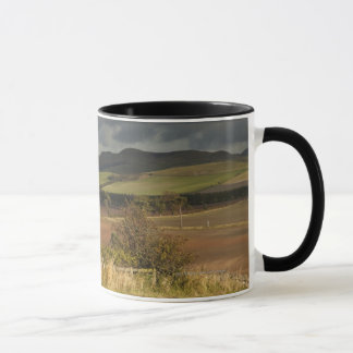 Rolling Hills And Mountains Under A Cloudy Sky Mug