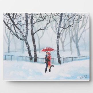 Romantic couple dancing in the snow red umbrella plaque