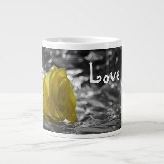 Rosa amarillo en amor del fondo de la plata del la taza de café gigante