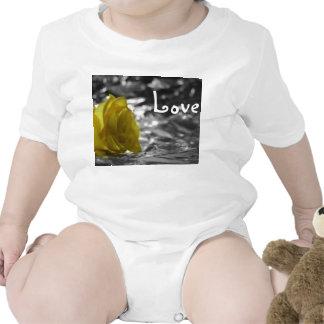 Rosa amarillo en amor del fondo de la plata del traje de bebé
