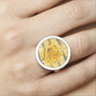 Rosa amarillo y anillo redondo de plata de la músi
