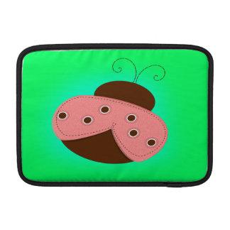 Rosa del dibujo animado y mariquita de Brown en un Fundas MacBook
