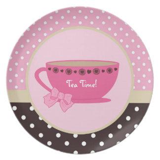 Rosa femenino de la taza de té del tiempo del té y plato de cena
