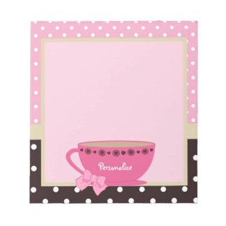 Rosa femenino de la taza de té y arco y nombre del bloc de notas