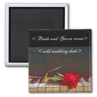 Rosa rojo que pone en el teclado de piano imán cuadrado