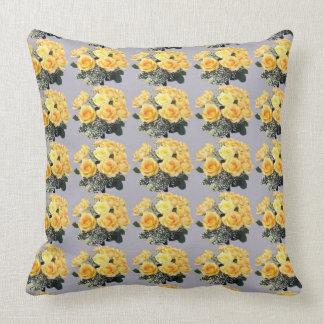 Rosas amarillos en la almohada de tiro gris del