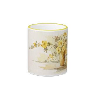 Rosas amarillos en un florero de la cerámica taza