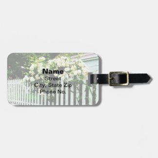 Rosas blancos en una valla de estacas etiquetas bolsa