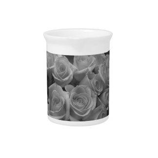 Rosas blancos y negros contra fondo manchado jarras