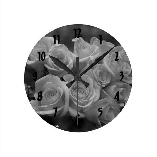 Rosas blancos y negros contra fondo manchado reloj redondo mediano