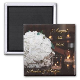 Rosas blancos y reserva de la luz de una vela el imán cuadrado