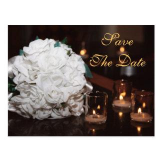 Rosas blancos y reserva de la luz de una vela la postales