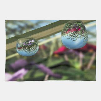 Rosas en la toalla de cocina de las gotas de agua