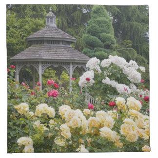 Rosas en rosaleda de la floración y del Gazebo en Servilleta Imprimida
