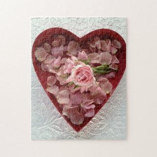 Rosas en una caja del corazón en rompecabezas de l