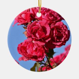 Rosas rojos en el cielo azul adorno navideño redondo de cerámica