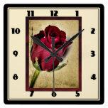 Rosas rojos majestuosos en fondo pardusco reloj cuadrado