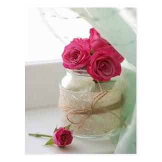 Rosas rosados bonitos en un tarro de cristal postales