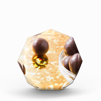 Round chocolate candy in small glass cup on color acrylic award