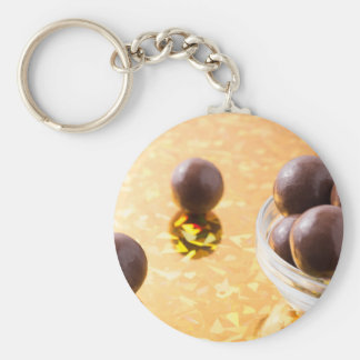 Round chocolate candy in small glass cup on color keychain