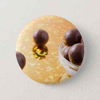 Round chocolate candy in small glass cup on color pinback button