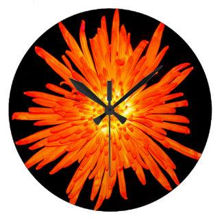 Round clock with an orange flower design.