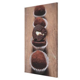 Row of chocolate truffles on wood canvas print