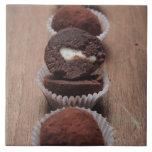 Row of chocolate truffles on wood ceramic tile