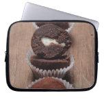 Row of chocolate truffles on wood laptop sleeve